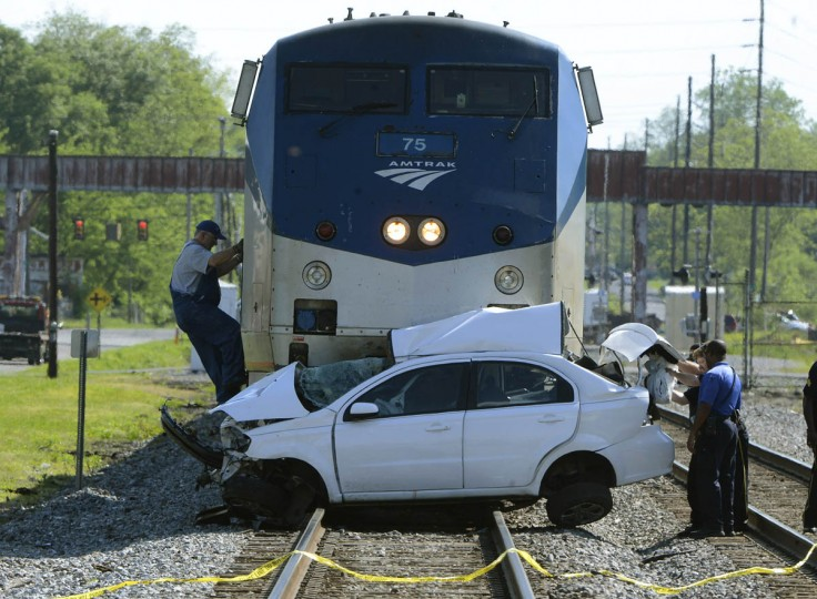 A conductor climbs to the cab of a locomotive after a collision between an Amtrak train and a car in Bessemer, Ala. The driver of the car drove around the crossing guards, according to Deputy Chief Mike Roper of the Bessemer Police Department. (Mark Almond/AL.com via AP)