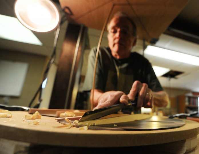 Luthier David MacCubbin files down the back struts of a guitar he's assembling. The filing strokes create small wooden curls that eventually cover the area beneath the apparatus. (Jon Sham/BSMG)