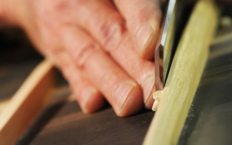 A detail shot shows luthier David MacCubbin's hands as he files down the back struts. (Jon Sham/BSMG)