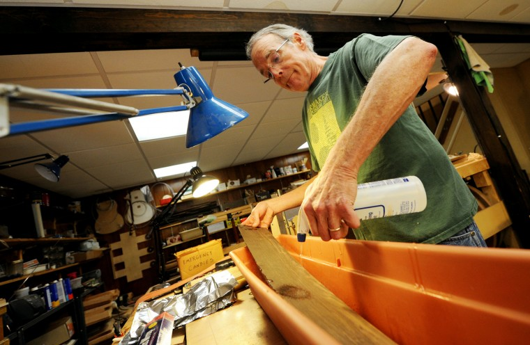 MacCubbin sprays a wooden panel to dampen it before bending it to form the curved side of the guitar. The panel will be wrapped in tin foil to hold in moisture and warmed on a heated bad to form the curvature. (Jon Sham/BSMG)