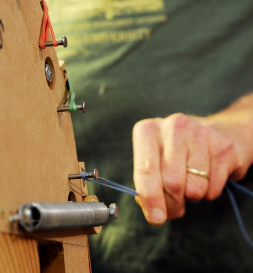 MacCubbin pulls a rubber band over a wooden block to hold in place a piece of an acoustic guitar he's building. MacCubbin first wets the wood, sets it in place, warms it for a few minutes and lets it dry overnight. (Jon Sham/BSMG)