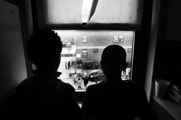 April 25: Two boys watch from their window at Glimor Homes as a massive march is led from the Freddie Gray vigil site to downtown. See more photos from the day here.
