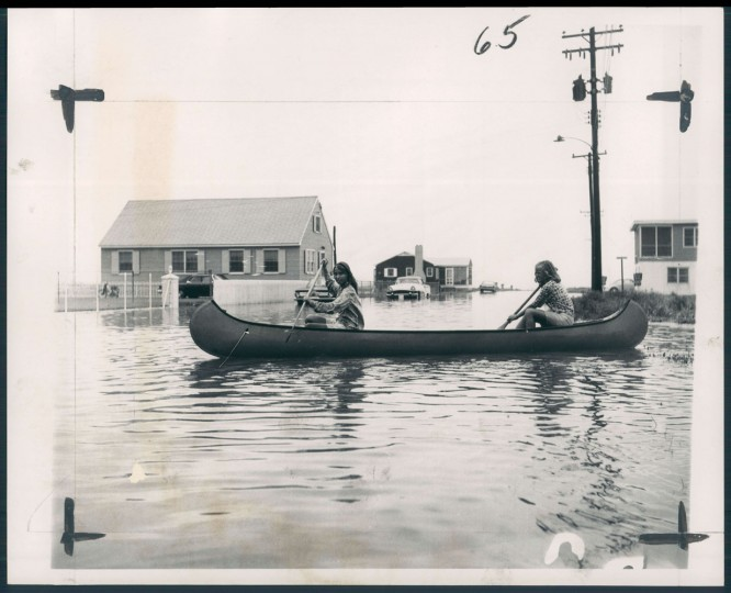 Paddling is easier than walking after 4 inches of rain turn OC streets into rivers, 1965.