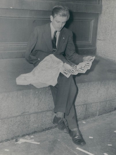 A discharged veteran reading news of surrender while looking at a map he picked up overseas. (Baltimore Sun archives)