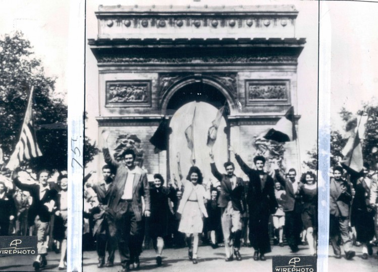 Waving flags of the Allied Nations, celebrating Parisians march out from under the Arc de Triomphe, along the Champs Eleysee, on V-E Day. (AP Wirephoto)