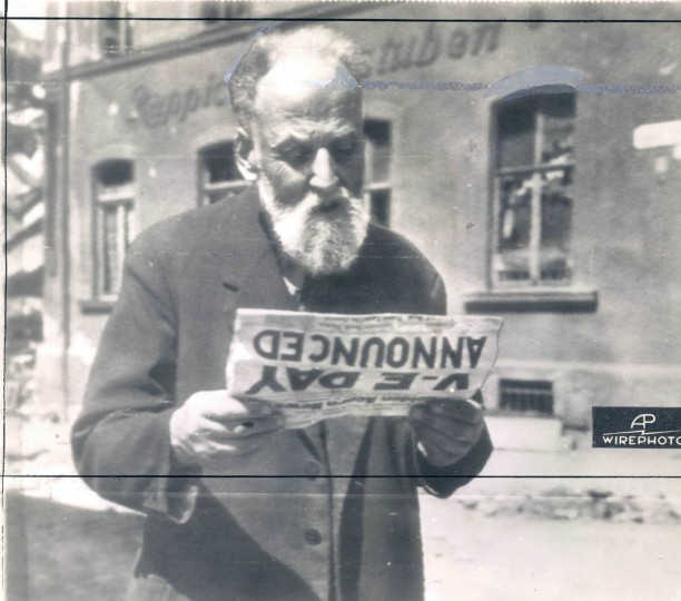 "This bearded German civilian at Falkenstein, Germany, on May 8, reads of complete surrender of his country's forces in the ""Golden Acorn,"" paper of the 87th Infantry Division of the U.S. 1st Army. (AP Wirephoto from Signal Corps RadioPhoto from London)"