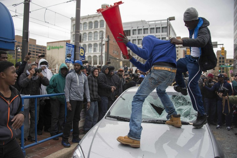 Demonstrators destroy the windshield of a Baltimore Police car as they protest the death Freddie Gray, an African American man who died of spinal cord injuries in police custody, in Baltimore, Maryland, April 25, 2015. Protesters returned to Baltimore's streets Saturday to vent outrage over the death of Gray on April 12. (Jim Watson/Getty Images)