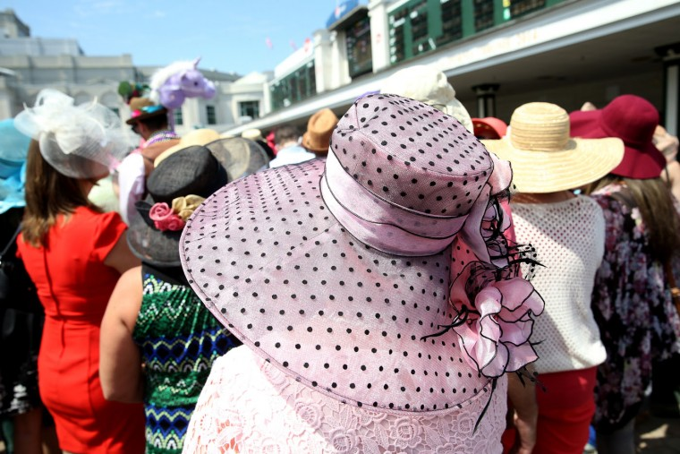 Women wearing a festive hats watch the paddock area prior to the 141st running of the Kentucky Derby at Churchill Downs on May 2, 2015 in Louisville, Kentucky. (Andy Lyons/Getty Images)
