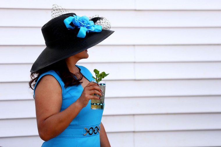 A woman wearing a festive hat and drinking a Mint Julep looks on prior to the 141st running of the Kentucky Derby at Churchill Downs on May 2, 2015 in Louisville, Kentucky. (Elsa/Getty Images)