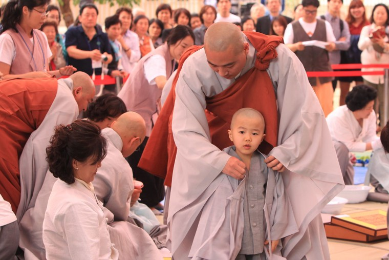 Children are dressed in robes by monks during the 'Children Becoming Buddhist Monks' ceremony forthcoming buddha's birthday at a Chogye temple on May 11, 2015 in Seoul, South Korea. Children have their hair shaved off during the 'Children Becoming Buddhist Monks' ceremony ahead of buddha's birthday at a Chogye temple. The children will stay at the temple to learn about Buddhism for 14 days. Buddha was born approximately 2,559 years ago, and although the exact date is unknown, Buddha's official birthday is celebrated on the full moon in May in South Korea, which is on May 25 this year. (Photo by Chung Sung-Jun/Getty Images)