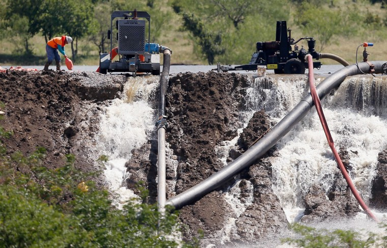 Workers tend to equipment used to pump water from Padera Lake as water pours over a temporary dam on May 27, 2015 in Midlothian, Texas. Officials feared that the temporary dam on Padera Lake would fail due to recent heavy rains in the area. Areas throughout Texas have expierenced flash flooding and numerous deaths due to weeks of heavy rainfall. (Photo by Tom Pennington/Getty Images)
