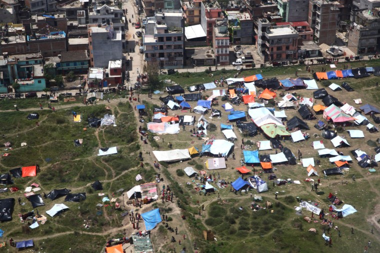 In this handout photograph taken released by The International Federation of Red Cross and Red Crescent Societies (IFRC) on April 27, 2015, shows an aerial view of temporary shelters in Kathmandu on April 27, 2015, following a 7.8 eaethquake which struck the Himalayan nation on April 25. Rescuers in Nepal are battling April 28, 2015, to reach remote communities devastated by a huge earthquake that has killed at least 4,310 people, as the impoverished country's leader said relief workers had still not reached many of the worst-hit areas. (Palani MOHAN/International Federation of Red Cross and Red Crescent Societies)