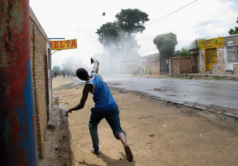 A protester throws stones at police during street battle in the Mugasa district of Bujumbura on Monday. Police fatally shot at least four demonstrators, including two in Musaga, in running battles with protesters angry at a bid by President Pierre Nkurunziza to extend his rule. (AYMERIC VINCENOT/AFP/Getty Images)