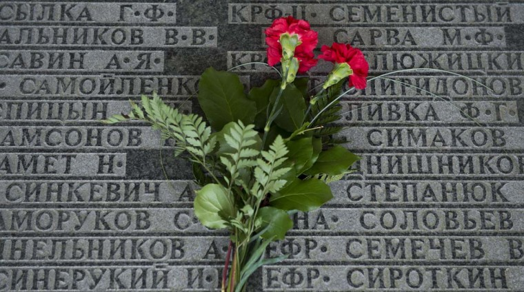 Flowers lay on a plaque engraved with the names of Soviet casualties at a Soviet war memorial in a cemetery for killed Soviet soldiers on the occasion of the 70th anniversary of the end of Second World War, in Lebus, eastern Germany, on May 8, 2015.  || CREDIT: JOHN MACDOUGALL - AFP/GETTY IMAGES
