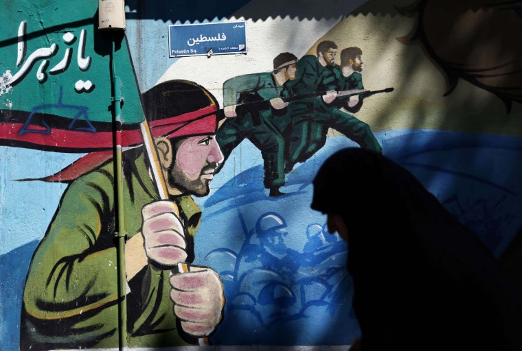 An Iranian woman walks past murals of Iranian soldiers marching during the Iran-Iraq war (1980-88), on May 8, 2015, on Palestine square in Tehran, after a demonstration to denounce the strikes by the Saudi led coalition against the Shiite rebellion in Yemen, where Iran is accused of meddling by Riyadh.  || CREDIT: BEHROUZ MEHRI - AFP/GETTY IMAGES