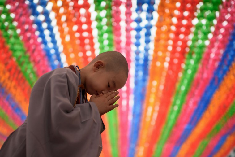 A young novice monk prays after having his head shaved by Buddhist monks during a ceremony entitled 'Children Becoming Buddhist Monks', at the Jogye temple in Seoul on May 11, 2015. Following the ceremony the children stay at the temple where they are taught about Buddhism, for two weeks, until Buddha's birthday on May 25. (AFP Photo/Ed Jones)
