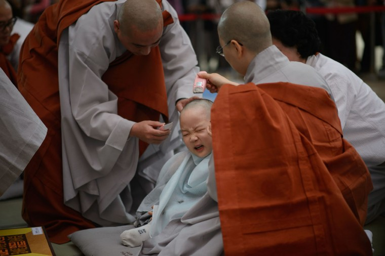 A child has his head shaved by Buddhist monks during a ceremony entitled 'Children Becoming Buddhist Monks', at the Jogye temple in Seoul on May 11, 2015. Following the ceremony the children stay at the temple where they are taught about Buddhism, for two weeks, until Buddha's birthday on May 25. (AFP Photo/Ed Jones)