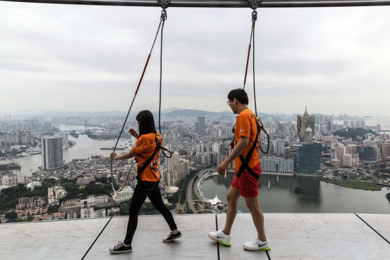 "Tourists take part in a ""sky walk"" on the rim of the 61st floor of the Macau Tower in Macau on Tuesday. The tower is the 10th highest freestanding tower in the world and the eighth tallest in Asia. (ANTHONY WALLACE/AFP/Getty Images)"