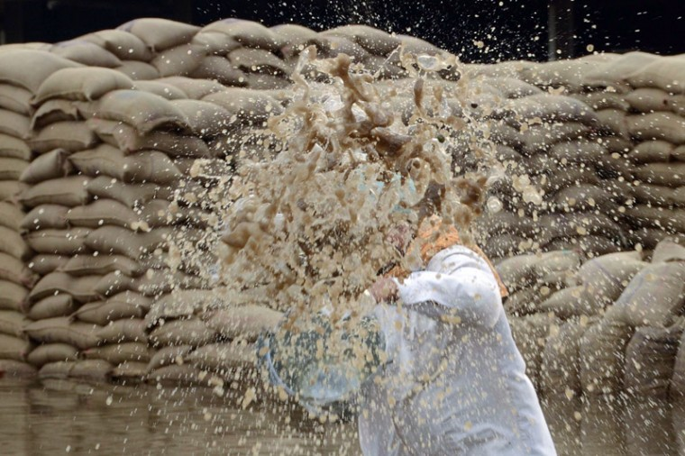 An Indian labourer is obscured by a bucket of rainwater he has thrown while clearing an area of standing water from flooded sacks of wheat at a grain distribution point in Amritsar on Tuesday after heavy rainfall in the northern state of Punjab. Punjab is India's largest wheat producing state, contributing nearly 70 percent of the national total. Farmers in the state have incurred huge losses as unseasonal rainfall damaged wheat crops, washing away prospects of a bumper production. (NARINDER NANU/AFP/Getty Images)