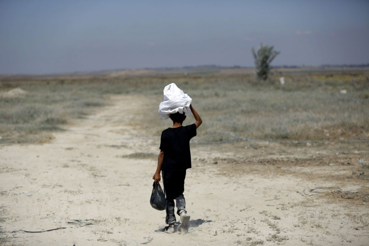"""A Palestinian boy walks in the Gaza Strip near the Nahal Oz border crossing with Israel as Palestinians mark the 67th anniversary of the """"Nakba"""" on May 15, 2015. """"Nakba"""" means in Arabic """"catastrophe"""" in reference to the birth of the state of Israel 67-years-ago in British-mandate Palestine, which led to the displacement of hundreds of thousands of Palestinians who either fled or were driven out of their homes during the 1948 war over Israel's creation. (MOHAMMED ABED/AFP/Getty Images)"""
