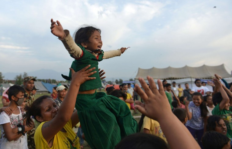 """A Nepalese mother and child participate in a """"laughter yoga"""" session to help relieve trauma among survivors of two earthquakes which struck the country in less than three weeks, in Kathmandu on May 15, 2015. Nearly 8,500 people have now been confirmed dead in the disaster, which destroyed more than half a million homes and left huge numbers of people without shelter with just weeks to go until the monsoon rains. (PRAKASH MATHEMA/AFP/Getty Images)"""