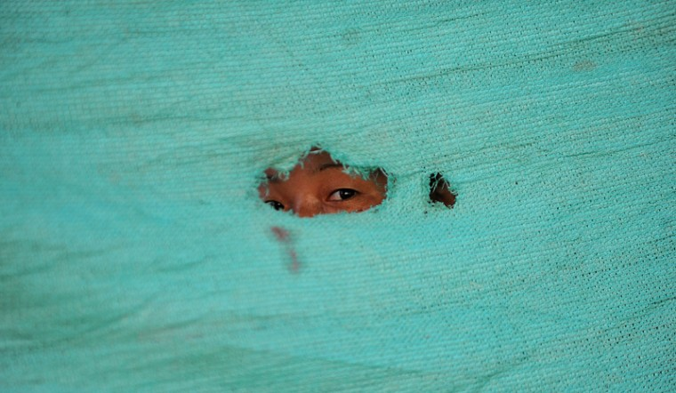 A Nepalese child looks on at a relief camp for survivors of the Nepal earthquake in Kathmandu on Tuesday. Nearly 8,500 people have now been confirmed dead in the disaster, which destroyed more than half a million homes and left huge numbers of people without shelter with just weeks to go until the monsoon rains. (Ishara S.KODIKARA/AFP/Getty Images)