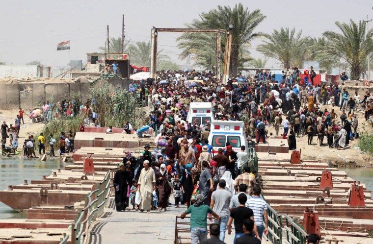 Iraqi residents from the city of Ramadi, who fled their homes as Islamic State (IS) group militants tightened their siege on the last government positions in the capital of Anbar province, wait to cross Bzeibez bridge, on the southwestern frontier of Baghdad, on May 20, 2015. Taking control of Ramadi would constitute the group's most important victory this year in Iraq, and would give the jihadists control of the capitals of two of its largest provinces. (Sabah Arar/Getty Images)