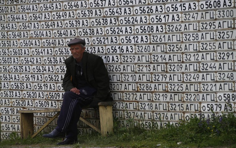 An elderly man sits on a bench near a fence made of old car numbers in Vank village not far from the city of Stepanakert in Armenian-seized Azerbaijani region of Nagorny Karabakh. (Andrey Golovanov/Getty Images)