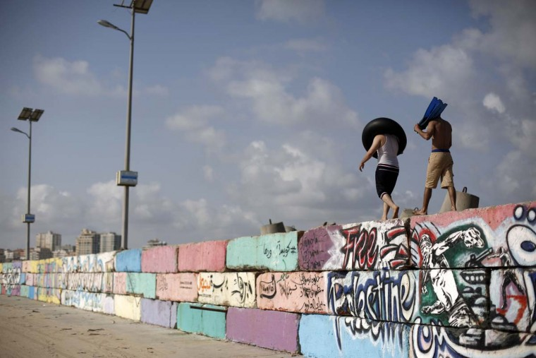 Palestinians walk on a wall on May 22, 2015 at the sea port in Gaza City.  || CREDIT: MOHAMMED ABED - AFP/GETTY IMAGES