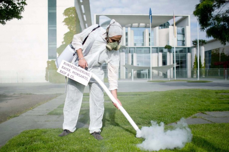 """An activist wearing a gas mask sprays in front of the chancellery with a device reading """"Government, Bayer, Monsanto, BASF and co"""" during an action on the International Day for Biological Diversity in Berlin, on May 22, 2015.  Jörg Carstensen - AFP/Getty Images"""