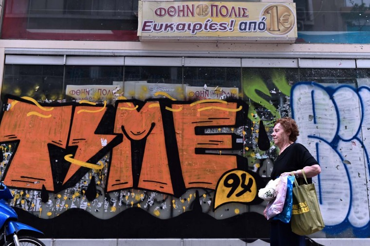 A woman walks past a shut-down store  in Athens on May 22, 2015.  German Chancellor Angela Merkel has dampened hopes for an end to marathon talks with Greece on a new loan deal as cash-strapped Athens said an agreement was possible by end month.  || CREDIT: LOUISA GOULIAMAKI - AFP/GETTY IMAGES