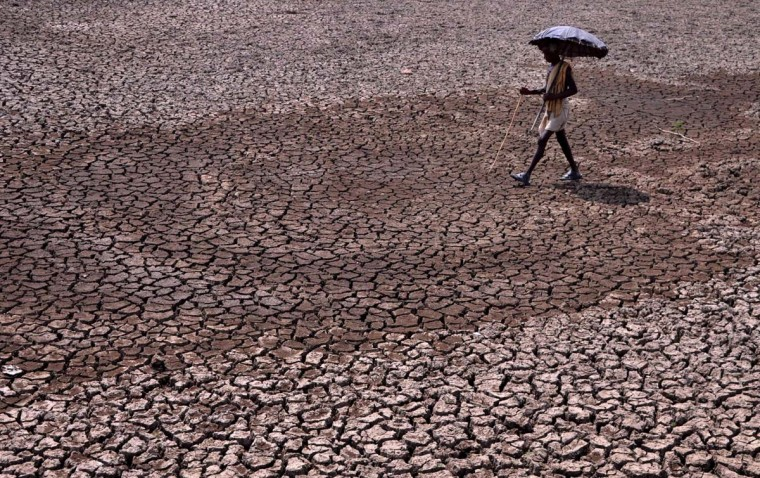 An Indian resident holds an umbrella as he walks across a dried-up pond on the outskirts of eastern Bhubaneswar on May 22, 2015. Many Indian cities face water shortages in the summer as temperatures soar above 40 degrees Celcius.  || CREDIT: ASIT KUMAR - AFP/GETTY IMAGES