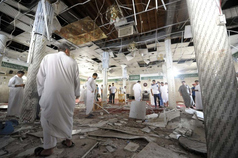 Saudi men gather around debris following a blast inside a mosque, in the mainly Shiite Saudi Gulf coastal town of Qatif, 400 kms east of Riyadh, on May 22, 2015. A suicide bomber targeted a Shiite mosque during Friday prayers in Kudeih in Shiite-majority Qatif district, the interior ministry said, with activists saying at least four worshippers were killed. AFP PHOTO / STRSTR/AFP/Getty Images ORG XMIT:
