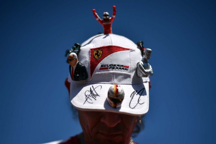 A supporter of the F1 Ferrari team sports various F1 related figurines on his cap as he waits for the drivers in the pit lane at the Monaco street circuit ahead of the Monaco Formula One Grand Prix in Monte-Carlo on May 22, 2015.  || CREDIT: ANDREJ ISAKOVIC - AFP/GETTY IMAGES