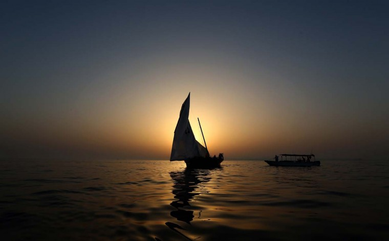 A dhow is seen at sunset during a training session on May 22, 2015 in the waters off the island of Sir Bu Nair on the eve of the Al-Gaffal 60 foot Traditional Dhow Sailing Race, in which boats will set sail off the island near the Iranian coast, until they reach the finish line at the Burj Al-Arab in Dubai. The 25th annual dhow sailing race has a total prize money of 10 million dirhams ($272,000).  || CREDIT: MARWAN NAAMANI - AFP/GETTY IMAGES