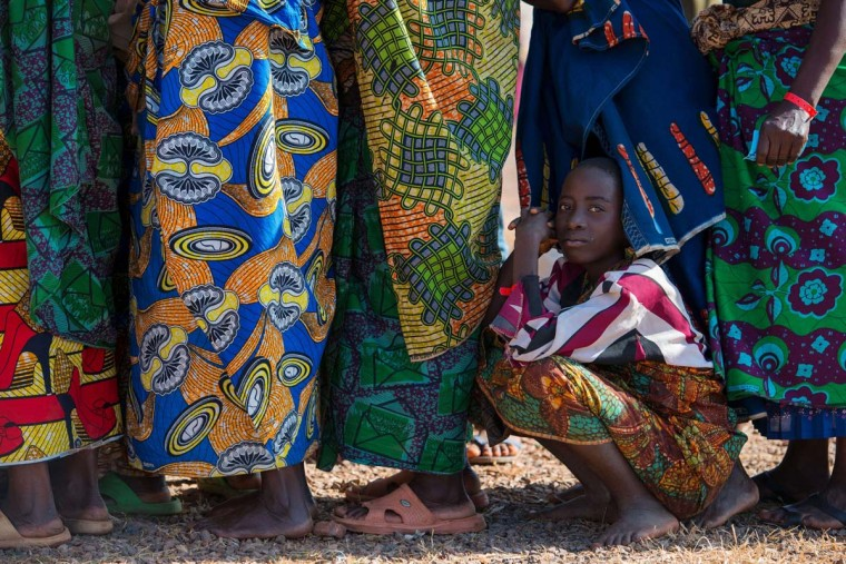 A girl stays out of the sun as Burundian refugees queue for vulnerability screening  in the Lake Tanganyika stadium in Kigoma on May 22, 2015. Some 3,000 cases of cholera have been reported in Tanzania, mainly among Burundian refugees fleeing political violence, the UN said on May 22, adding that up to 400 new cases were being counted daily. So far, 31 people have died of the water-born disease in the area around the western Tanzanian border town Kaguna, which has been flooded with refugees, the UN refugee agency said.  || CREDIT: DANIEL HAYDUK - AFP/GETTY IMAGES