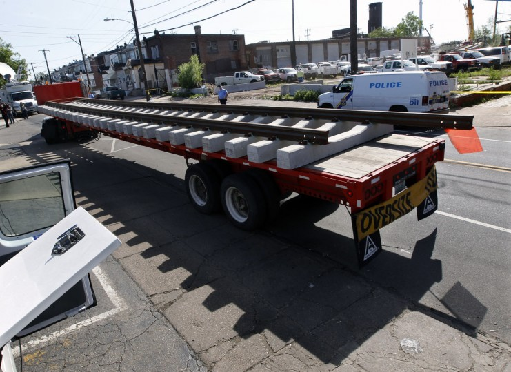 A flat bed truck hauls a section of new railroad track to the site of Tuesday's deadly train derailment, Thursday, May 14, 2015, in Philadelphia. At least seven people are dead and more than 200 people aboard injured, when the New York City bound Amtrak train derailed. Federal investigators have determined that the train was barreling through the city at 106 mph before it ran off the rails along a sharp curve where the speed limit drops to just 50 mph. (AP Photo/Mel Evans)