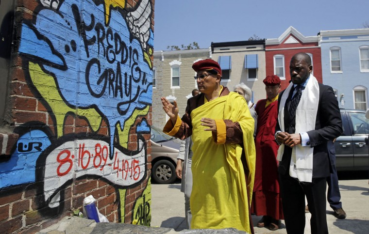 The Gyalwang Drukpa, left, the Buddhist leader of South Asia, prays at the site of Freddie Gray's arrest in Baltimore alongside the Rev. Jamal Bryant, right, and other faith and community leaders, Thursday, May 7, 2015. The group toured the neighborhood and visited a store that was damaged by fire during last month's unrest, following the death of Gray, who suffered a fatal spinal injury while in police custody. (AP Photo/Patrick Semansky)