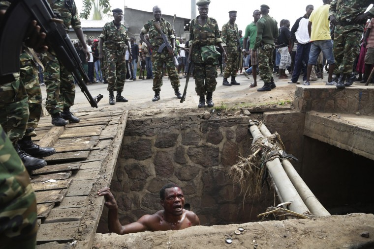 Jean Claude Niyonzima, a suspected member of the ruling party's Imbonerakure youth militia, pleads with soldiers to protect him from a mob of demonstrators after he emerged from hiding in a sewer in the Cibitoke district of Bujumbura, Burundi, Thursday May 7, 2015. Niyonzima fled from his house into a sewer under a hail of stones thrown by a mob protesting against President Pierre Nkurunziza's decision to seek a third term in office. At least one protestor has died in clashes with the widely feared Imbonerakure militias and police, sending scores to the streets seeking revenge. Jean Claude Niyonzima managed to flee from his house under a hail of stones into a covered sewer, where he remained till the army fired shots into the air to disperse the crowd. (AP Photo/Jerome Delay)