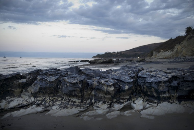 Rocks are covered with oil on the beach at Refugio State Beach, north of Goleta, Calif., Thursday, May 21, 2015. More than 6,000 gallons of oil had been raked, skimmed and vacuumed from a spill that stretched across 9 miles of California coast in a cleanup effort that is now going 24 hours a day, officials said, but that's just a fraction of the sticky, stinking goo that escaped from a broken pipeline. (AP Photo/Jae C. Hong)