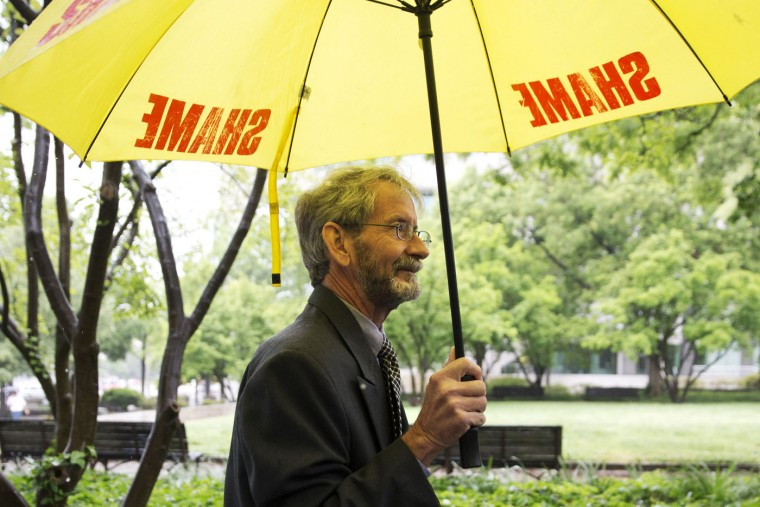 "Carrying an umbrella that says ""shame"" on it, Douglas Hughes of Florida arrives at federal court in Washington, Thursday, May 21, 2015. Hughes, who flew a gyrocopter through some of America's most restricted airspace before landing at the Capitol pleaded not guilty on Thursday to the six charges he faces. (AP Photo/Jacquelyn Martin)"