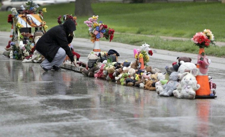 Lala Moore pauses silently before helping others remove items left at a makeshift memorial to Michael Brown Wednesday, May 20, 2015, in Ferguson, Mo. The memorial that has marked the place where Brown was fatally shot by a police officer in August has been removed and will be replaced with a permanent plaque, Ferguson's Mayor James Knowles said Wednesday. (AP Photo/Jeff Roberson)