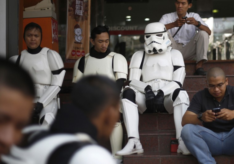 "Indonesian men dressed as stormtroopers from the""Star Wars"" movies take a break between performances during a promotional event at a shopping mall in Jakarta, Indonesia, on Tuesday. (Dita Alangkara/AP)"