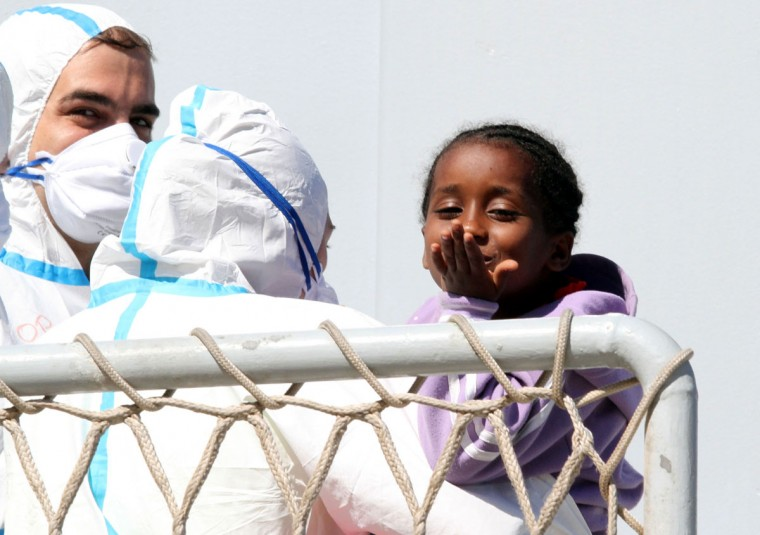 A child blows a kiss as migrants disembark from the Italian Navy frigate Bersagliere at the Reggio Calabria harbor, Italy, Monday, May 4, 2015. Italy's Coast Guard and Navy as well as tugs and other commercial vessels joined forces to rescue migrants in at least 16 boats Sunday, saving hundreds of them and recovering 10 bodies off Libya's coast, as smugglers took advantage of calm seas to send packed vessels across the Mediterranean. Sunday's drama at sea came a day after 3,690 migrants were saved from smugglers' boats. Most of those migrants are still being taken to southern Italian ports even as the fresh rescues were taking place. (AP Photo/Adriana Sapone)