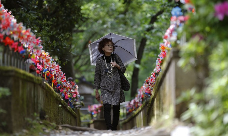 "A woman walks along the rows of small stone statues of ""jizo"" representing the unborn children at Zojoji Buddhist temple in Tokyo, Monday, May 4, 2015. Jizo, which is one of the most beloved figures of Japanese Buddhism, are believed to protect deceased children. ((AP Photo/Shizuo Kambayashi)"