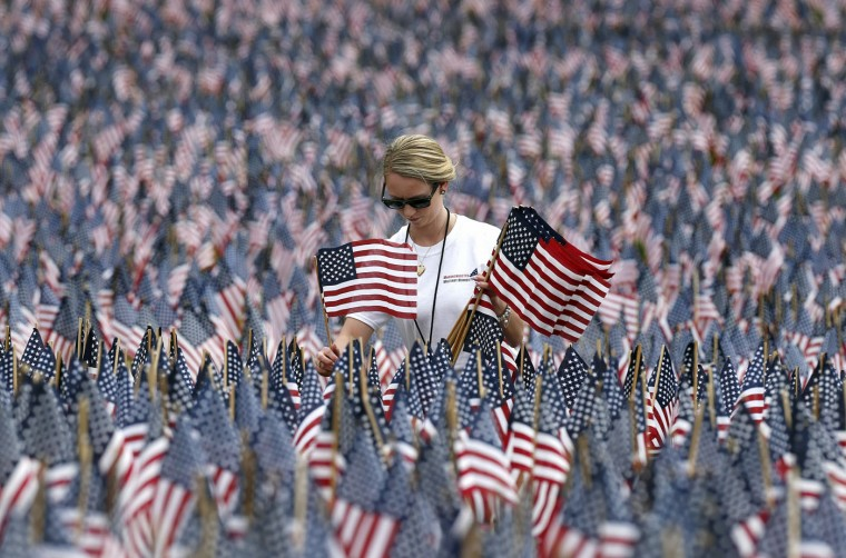 Shannon Day, of Boston, a volunteer with Massachusetts Military Heroes Fund, replaces damaged flags in the fund's flag garden on Boston Common in Boston, ahead of Memorial Day, Thursday, May 21 2015. Each of the approximately 37,000 flags represents a Massachusetts military member who died in service from the Revolutionary War to the present. (AP Photo/Michael Dwyer)