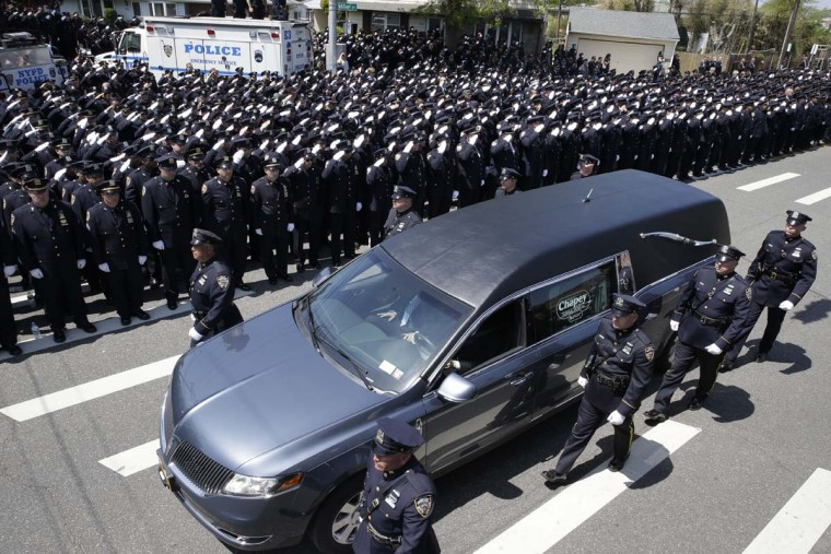 Police officers salute as the procession for New York City Police officer Brian Moore passes after his funeral mass,  Friday, May 8, 2015, at the St. James Roman Catholic church in Seaford, N.Y. The 25-year-old died Monday, two days after he was shot in Queens.    || CREDIT: MARY ALTAFFER - AP PHOTO