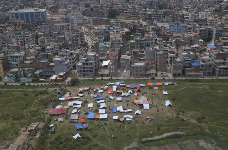 Tents are seen from an airplane window in an open field next to Tribhuwan International Airport Sunday, April 26, 2015, a day after a massive earthquake in Kathmandu, Nepal. A strong earthquake shook Nepal's capital and the densely populated Kathmandu Valley before noon Saturday, causing extensive damage with toppled walls and collapsed buildings, officials said. (AP Photo/Wally Santana)