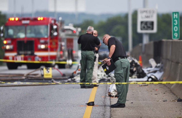 Investigators look at the wreckage of a plane that crashed on Interstate 285, Friday, May 8, 2015, in Doraville, Ga. A small passenger airplane crashed into an Atlanta interstate Friday, killing all four people aboard and starting an intense fire on the busy road, authorities said.  || CREDIT: DAVID GOLDMAN - AP PHOTO
