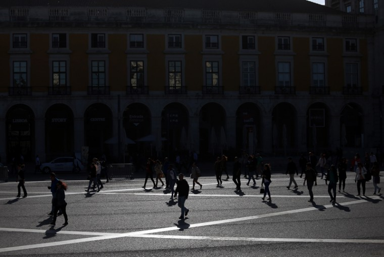 Commuters cast their shadows against the ground as they walk along Comercio square during a 24-hour strike by Lisbon's subway workers, in Lisbon, Portugal, on Tuesday. The strike was against pay cuts and the public company's possible privatisation. (Francisco Seco/AP)